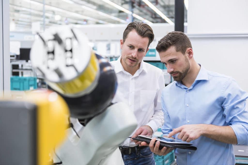Zwei Mitarbeiter aus dem Qualitätsmanagement überprüfen die Funktionalitäten eines Roboters mit einem Tablet